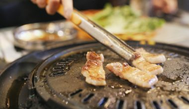 Cooking meat on a Korean BBQ grill using metal tongs