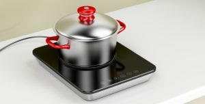 Small portable induction stovetop with a stainless steel pot on top